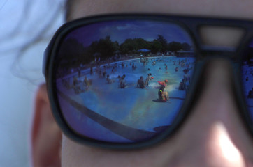 The 'Grugabad' open-air swimming pool is reflected in a woman's sunglasses on a hot summer day in Essen