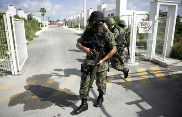 Soldiers inspect a neighborhood near a crime scene in Cancun
