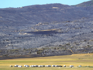 Trailers that were evacuated from fire area sit in field as the aftermath of the Wood Hollow Fire is seen in the background north of Fairview
