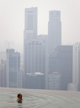 A hotel guest swims in an infinity pool overlooking the haze-covered skyline in Singapore