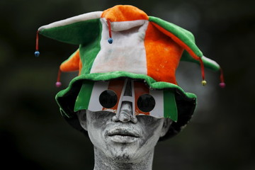 A man painted in the Ivory Coast flag colors looks on during the commemoration of Ivory Coast's 55th Independence Day in Abidjan