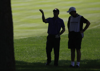 Britain's Luke Donald confers with his caddie McClaren in the rough on the 18th hole during the third round of the WGC Bridgestone Invitational PGA golf tournament at Firestone Country Club in Akron