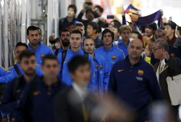 Barcelona's Iniesta and his team mates walk upon their team's arrival at Narita International airport near Tokyo