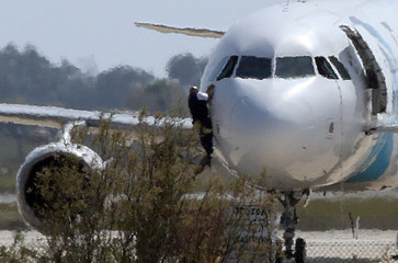 A man climbs out of the cockpit window of the hijacked Egyptair Airbus A320 at Larnaca Airport in Larnaca, Cyprus