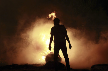 A protester starts a fire during clashes with riot police along a road at Kornish El Nile which leads to the U.S. embassy, near Tahrir Square in Cairo
