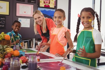 smiling teacher and schoolkids standing in drawing classroom