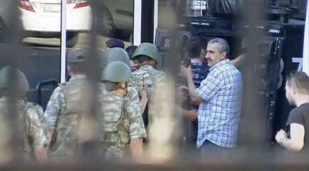 A still image from video shows soldiers surrendering to the police and handing over their weapons and flak jackets, as seen through bars of a fence at TRT state television after a failed coup attempt, in Istanbul