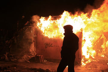 """A migrant stands near a burning makeshift shelter set ablaze in protest against the partial dismantlement of the camp for migrants called the """"jungle"""", in Calais"""
