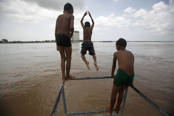Boys jump into the Chaktomok river in front of the Royal Palace in Phnom Penh