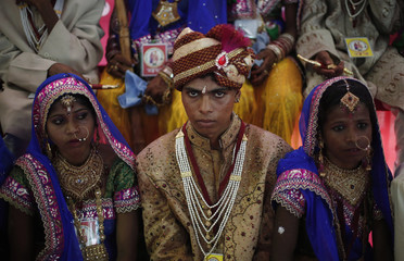 A groom sits next to brides as they pose for pictures during a mass wedding ceremony at Ramlila ground in New Delhi