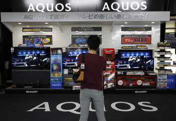 A man looks at Sharp Corp's Aquos television sets displayed at an electronics store in Tokyo