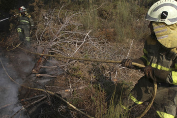 Firefighters try to extinguish a forest fire in Boboras in the northwest Spanish region of Galicia