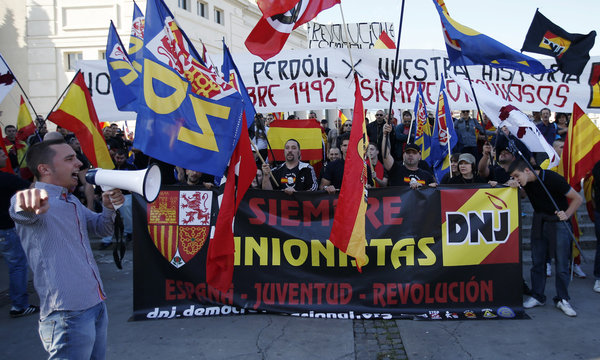Ultra right wing demonstrators wave flags as a man points and shout slogans against journalists during Spain's National Day in Barcelona