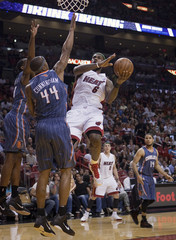 Miami Heat's LeBron James goes for a layup as Charlotte Bobcats' Cunningham defends during their NBA basketball game in Miami