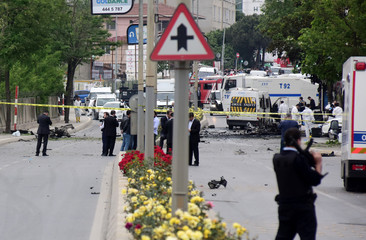 Police forensic experts examine the scene following a vehicle explosion near a military facility in Istanbul