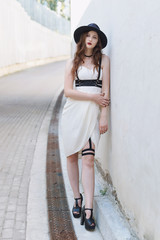 Young beautiful sexy woman wearing trendy outfit, white dress, black hat and leather swordbelt. Longhaired brunette posing in the city street on a sunny day. Outdoor fashion photography