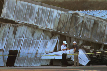Workers stand near the wreckage of a twin-engine Cessna Citation 525A aircraft before it is extracted from inside a collapsed hangar it slammed into and burst into flames, after it touched down last night, in Santa Monica