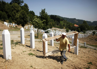 A worker carries a wooden frame while preparing graves for a ceremony at a memorial centre for Srebrenica Massacre victims in Potocari