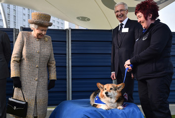 Britain's Queen Elizabeth looks at a Corgi dog as television presenter Paul O'Grady smiles during the Queen's visit to Battersea Dogs & Cats Home in London
