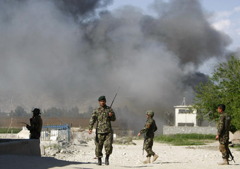 Soldiers from the Afghan National Army keep watch near PRT as smoke rises from the site of an attack in Jalalabad