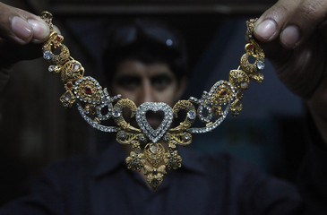 A man displays a gold necklace decorated with precious stones at a jewellery shop in Lahore