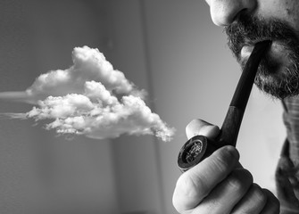 Surreal photo of man smoking pipe with clouds