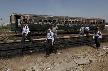 Students walk past the doused car of a train which caught fire as they head home along a railway track at Cantonment railway station in Karachi