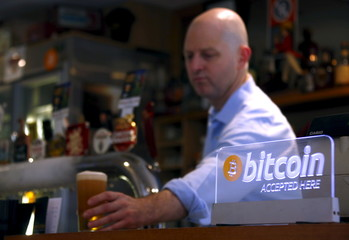 Publican Grant Fairweather places a beer on the bar next to a Bitcoin sign as he serves a customer in Sydney, Australia
