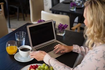 Woman holding coffee cup while using laptop