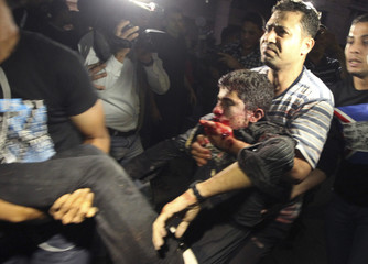 A wounded Palestinian is carried into a hospital in Gaza City following Israeli shelling