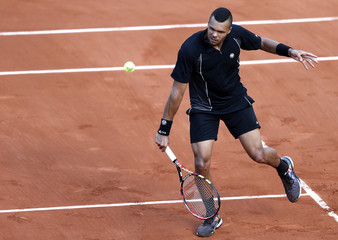 Jo-Wilfried Tsonga of France plays a shot to Christian Lindell of Sweden during their men's singles match at the French Open tennis tournament at the Roland Garros stadium in Paris