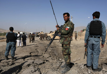 Afghan policemen stand near a crater at the scene of a suicide attack in Maidan Shar