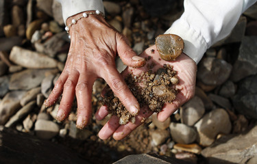 Liz Krikowa looks for iron stones associated with gold at Shoalhaven River near Braidwood