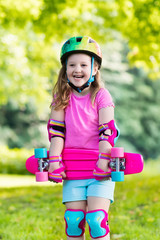 Child riding skateboard in summer park