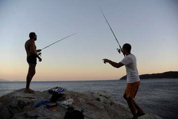 Men fish on a rocky coast near the village of Marathon, north-east of Athens