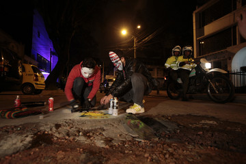 Street artists create graffiti on the road to draw attention to the deplorable road conditions in Bogota