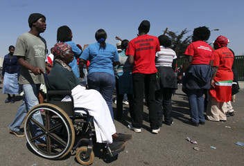 A patient is wheeled past South African state workers in a strike outside the Natalspruit hospital, east of Johannesburg