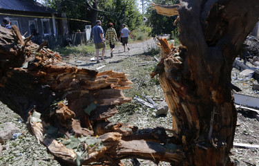 Local residents walk past a tree damaged in a recent shelling in Donetsk