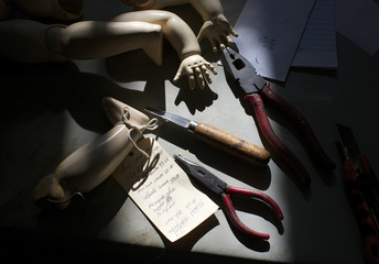 Doll limbs and hand tools are pictured in the afternoon sun on the work bench of Geoff Chapman, 'Head Surgeon' and owner of Sydney's Doll Hospital