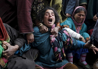Relatives mourn during the funeral of the victims who died after a hillside collapsed onto a house at Ledhan village