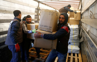 Workers carry humanitarian supplies to a Syria-bound truck at a UN transhipment hub in Reyhanli, near the Turkish-Syrian border in Hatay province