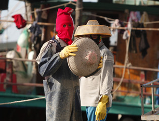 A man wearing a red face cover prepares to put on a hat as he repairs fishing nets at a port in the city of Dongfang on the western side of China's palm-fringed island province of Hainan