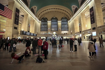 Children play on the ground as people make their way through Grand Central Terminal during the busy Thanksgiving holiday weekend in the Manhattan borough of New York