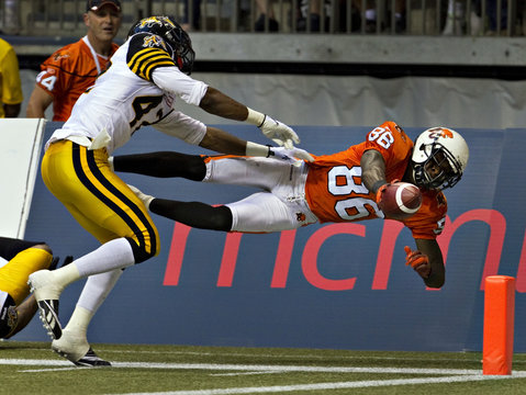 BC lions wide receiver Taylor dives for the goal line as Hamilton Tiger-Cats defensive back Brown moves in during CFL football game in Vancouver