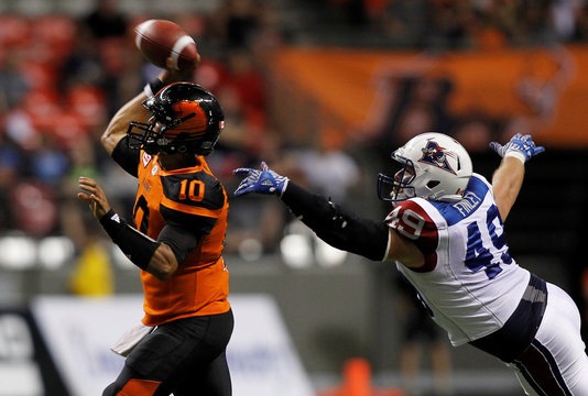 B.C Lions QB Jonathon Jennings throws the ball while being chased by Montreal Alouettes DL Jeffrey Finley during the second half of their CFL football game in Vancouver