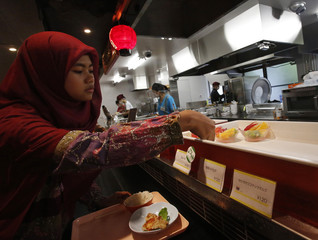 A Muslim foreign student picks a bowl of cut fruits at the halal section of a dining hall in the Kanda University of International studies in Chiba
