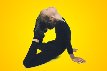 The little girl on the floor does gymnastics exercises on yellow background