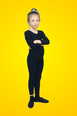 Little girl in a dance costume on yellow background
