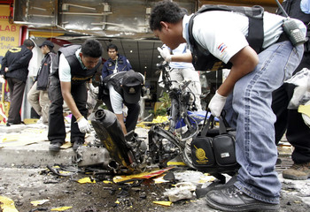 Police officers inspect the site of a bomb attack near a car showroom in Yala province, 1,100 km (680 miles) south of Bangkok