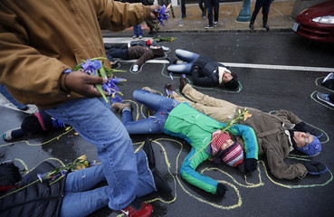 A demonstrator sprinklers flowers over people laying on the ground with chalk outlines to represent a mock crime scene during a protest marking the 100th day since the shooting death of Michael Brown in St. Louis